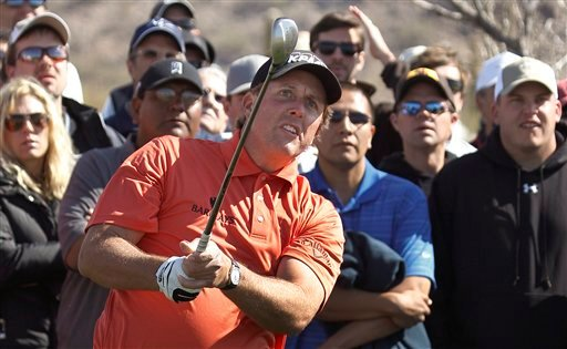 Phil Mickelson watches his approach shot on the second hole while playing Rickie Fowler during the second round of the Match Play Championship golf tournament.