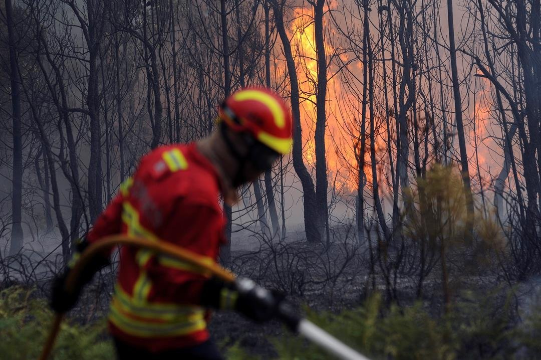Portuguese firefighters work to stop a forest fire from reaching the village of Figueiro dos Vinhos in central Portugal, Sunday.  (AP Photo/Paulo Duarte)