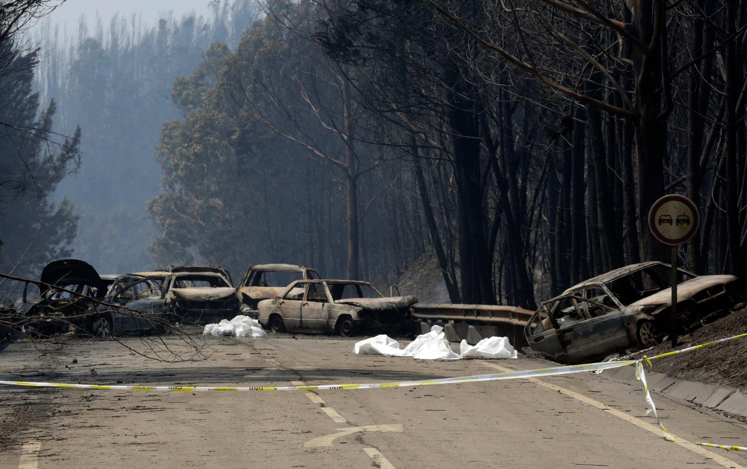 Burnt cars block the road between Castanheira de Pera and Figueiro dos Vinhos, central Portugal, Sunday.  (AP Photo/Armando Franca)