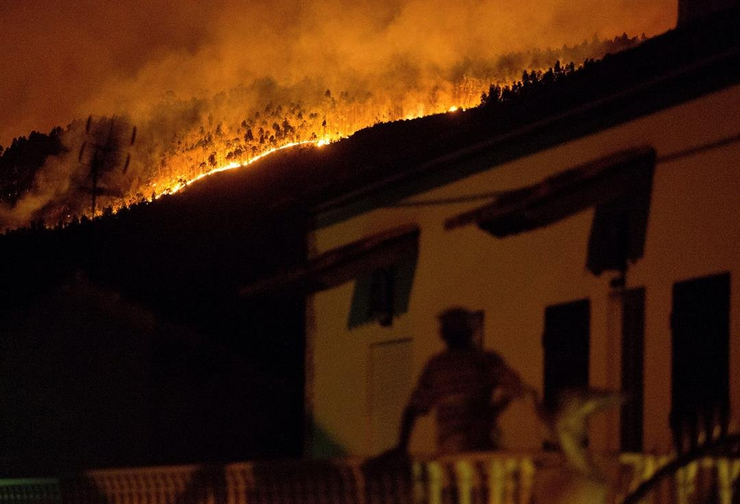 A man on the balcony of a house looks up at a forest fire raging on a hillside above the village of Avelar, central Portugal, before sunrise Sunday. (AP Photo/Armando Franca)