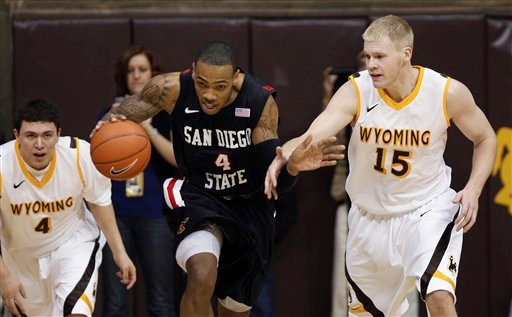 San Diego State forward Malcolm Thomas (4) brings the ball up between Wyoming's Francisco Cruz (4) and Adam Waddell (15) during an NCAA college basketball game Tuesday, March 1, 2011, in Laramie, Wyo.