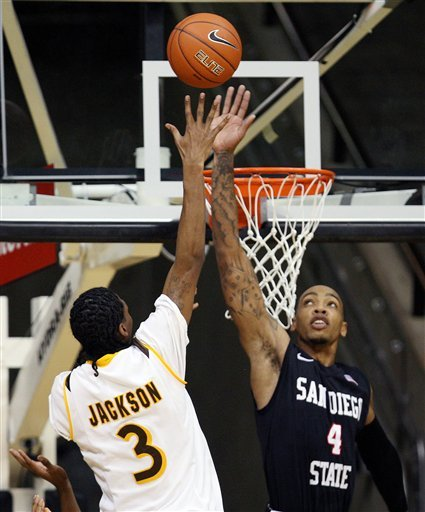 San Diego State forward Malcolm Thomas tries to block the shot of Wyoming's Desmar Jackson.