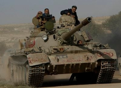 Libyan rebels sit on their tank as they going forward to battle against pro-Moaamar Gadhafi fighters, in the town of Brega, east of Libya, on Wednesday, March 2, 2011.