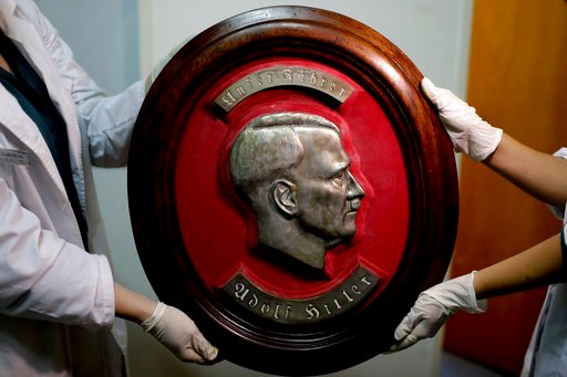 Members of the federal police show a bust relief portrait of Nazi leader Adolf Hitler at the Interpol headquarters in Buenos Aires, Argentina, Friday, June 16, 2017. (AP Photo/Natacha Pisarenko)