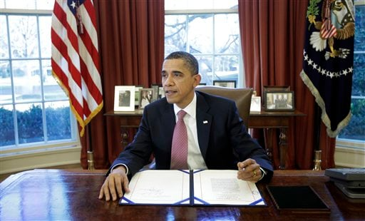 President Barack Obama signs the two-week funding bill averting a government shutdown in the Oval Office at the White House in Washington, Wednesday, March 2, 2011.