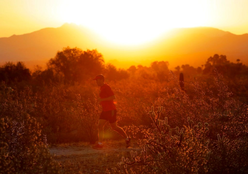 A man runs through the desert at sunrise, Friday, June 16, 2017, in Phoenix. A record heat wave is rolling into Arizona, Nevada and California, threatening to bring 120-degree temperatures to Phoenix by early next week. (AP Photo/Matt York)