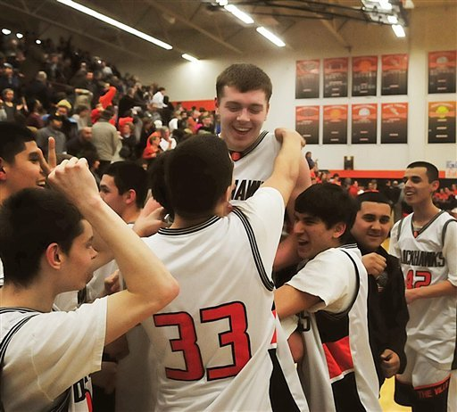 Members of the Fennville High School basketball team lift Wes Leonard, top, after he made a game-winning layup in overtime against Bridgman, in Fennville, Mich. , Thursday night, March 3, 2011.