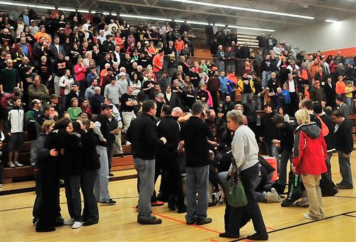 Fans look on as trainers and coaches try to revive Fennville High School basketball player Wes Leonard.