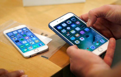 FILE - In this Friday, Sept. 16, 2016, file photo, a customer sets up his new iPhone 7 Plus, right, as he switches from the iPhone 6 at the Apple Store on Michigan Avenue. (AP Photo/Kiichiro Sato, File)