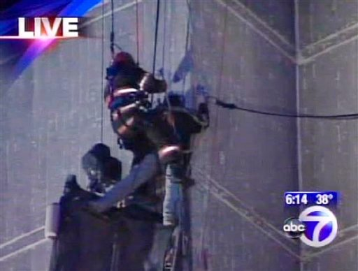 This frame grab taken from video released by WABC-TV 7 in New York shows a firefighter securing the second of two workers who were dangling from safety ropes about 12 stories up on the side of a building after their scaffolding apparently collapsed.