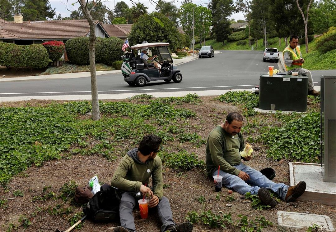 FILE - In this May 4, 2016, file photo, Duncan Wallace drives a golf cart from his house to his golf club as a group of landscape workers take a break in Vista, Calif.  (AP Photo/Gregory Bull, File)