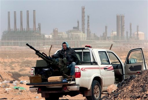 March 5, 2011 file photo: an anti-government rebel sits with an anti-aircraft weapon in front an oil refinery, after the capture of the oil town of Ras Lanouf, eastern Libya. (AP Photo/Hussein Malla, File)
