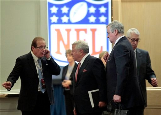 New England Patriots owner Robert Kraft, center talks with an unidentified man, left, as Carolina Panthers owner Jerry Richardson, right, looks on after a meeting with NFL owners at a hotel in Chantilly, Va.