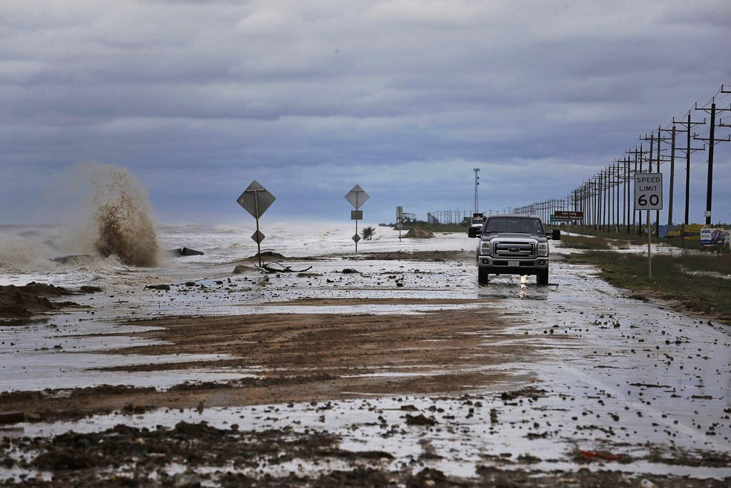 Vehicles navigate past waves and debris washing over State Highway 87 as Tropical Storm Cindy approaches Wednesday, June 21, 2017, in High Island, Texas. (Michael Ciaglo/Houston Chronicle via AP)