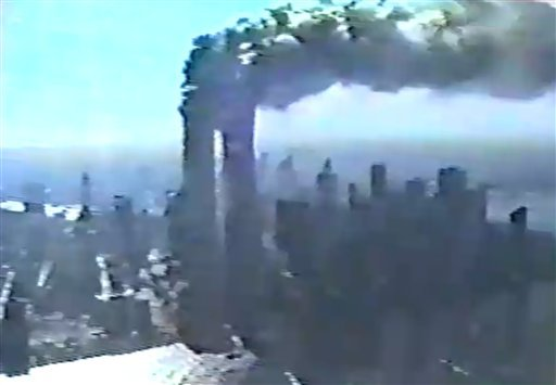 In this image made from New York Police Department video posted on the Internet of the World Trade Center attack, smoke engulfs the twin towers after being hit by commercial airliners, as videotaped from a NYPD helicopter on Sept. 11, 2001.