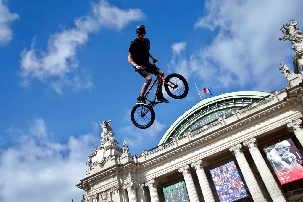 Belgian biker Kenneth Tancre performs outside the Grand Palais museum in Paris, Friday, June 23, 2017. Paris is aiming to boost its bid for the 2024 Olympics by turning some of its world-famous landmarks over to sports for two days, with 100-meter races o