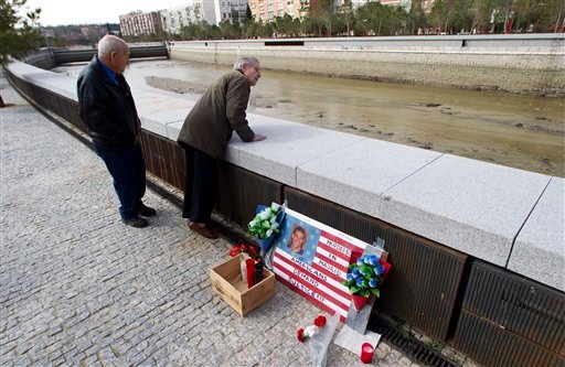Local resident Manuel Calderon, a retired military engineer, right looks over into the river Manzanares beside a memorial of flowers and candles for U.S. student Austin Bice, in Madrid March 9, 2011. (AP Photo/Paul White)
