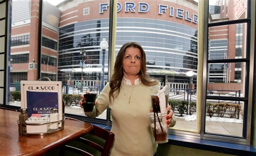 In this photo taken Friday, March 4, 2011, Elwood Bar & Grill manager Liz Markle clears a table with a view of Ford Field in Detroit, home to NFL football's Detroit Lions.