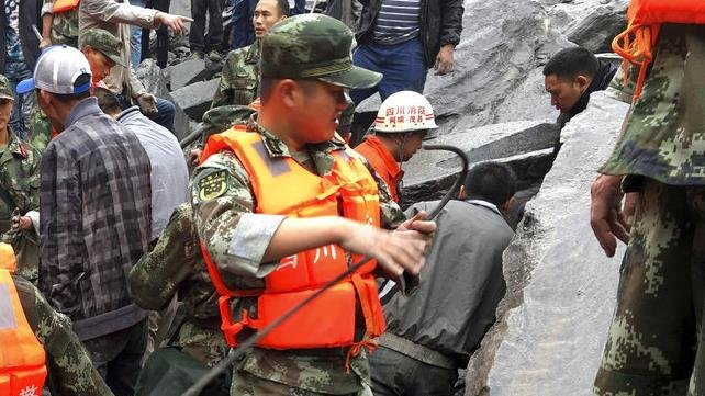 Emergency personnel work at the site of a massive landslide in Xinmo village in Maoxian County in southwestern China's Sichuan Province, Saturday, June 24, 2017