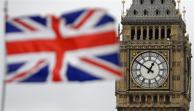 The British flag blown by the wind near to Big Ben's clock tower.
