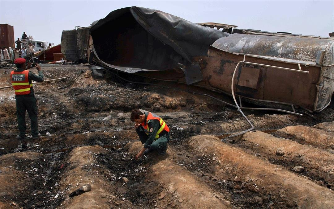 Pakistani rescue workers examine the site of an oil tanker explosion at a highway near Bahawalpur, Pakistan, Sunday, June 25, 2017. (AP Photo/Iram Asim)