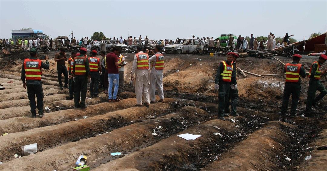 Pakistani rescue workers gather at the site of an oil tanker explosion at a highway near Bahawalpur, Pakistan, Sunday, June 25, 2017. (AP Photo/Iram Asim)