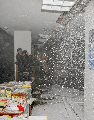 © People at a book store react as the store's ceiling falls in Sendai, northern Japan.