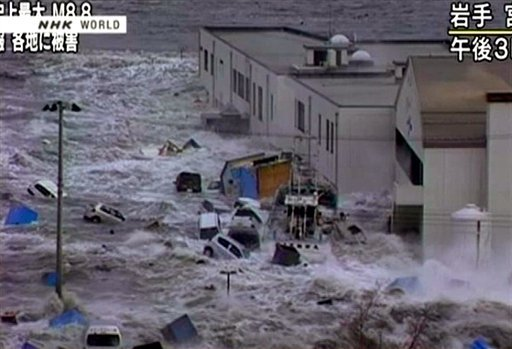 In this video image taken from Japan's NHK TV, a tsunami surge sweeps cars, boats and other debris against a building in Miyaku City, Iwate Prefecture Japan Friday March 11, 2011 following a massive earth quake.