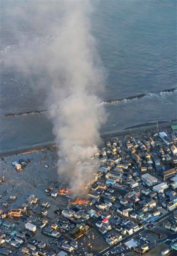 Fire smokes billow from residences as a coastal area is flooded by waters after a tsunami in Iwaki, Fukushima prefecture (state).