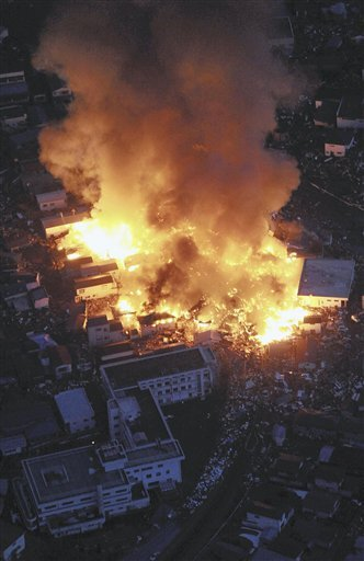 © Flames rise from houses on fire after powerful earthquakes hit Yamada, Iwate Prefecture, northern Japan, Friday, March 11, 2011.