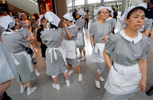 Hotel employees gather at the hotel's entrance in Tokyo, Japan as an earthquake hits Friday, March 11, 2011.