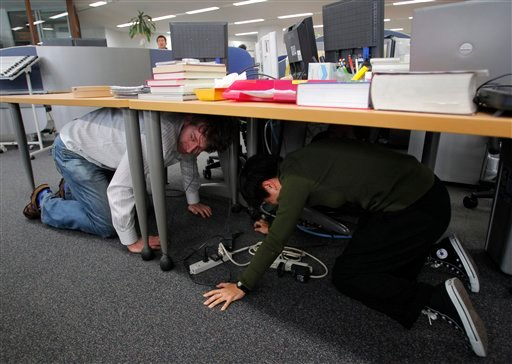 Reporters at the Associated Press Tokyo Bureau in Tokyo take shelter under a table while a strong earthquake strikes eastern Japan Friday afternoon, March 11, 2011. (AP Photo/Itsuo Inouye)