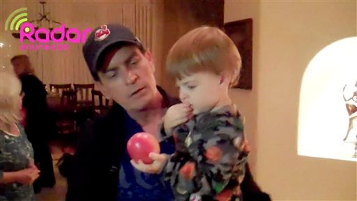 In this image from video released by RadarOnline.com, Charlie Sheen holds one of his 23-month-old twins before they are removed from his Hollywood Hills home late Tuesday, March 1, 2011 in Los Angeles.