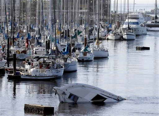 A boat sinks into the ocean in the aftermath of the surge caused by a tsunami on the harbor in Santa Cruz, Calif.