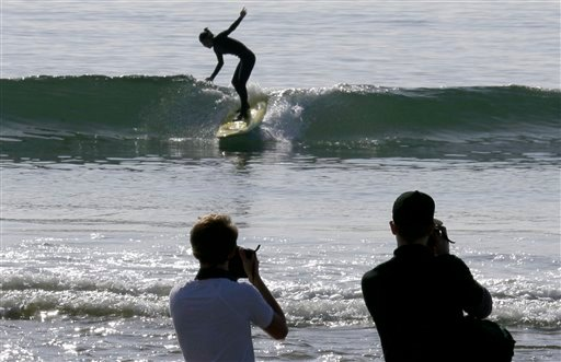 Visitors take photos as a surfer takes a wave at about the time the effects of a tsunami were expected, at Surfrider Beach in Malibu, Calif.