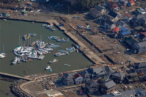 Residential houses, buildings and boats get washed away by floods at a port in Sendai, northern Japan, Saturday, March 12, 2011. (AP Photo/Itsuo Inouye)