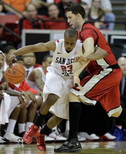 San Diego State's D.J. Gay, left, is fouled by UNLV's Carlos Lopez during the second half of an NCAA college basketball game in the semifinals of the Mountain West Conference tournament, Friday, March 11, 2011, in Las Vegas.