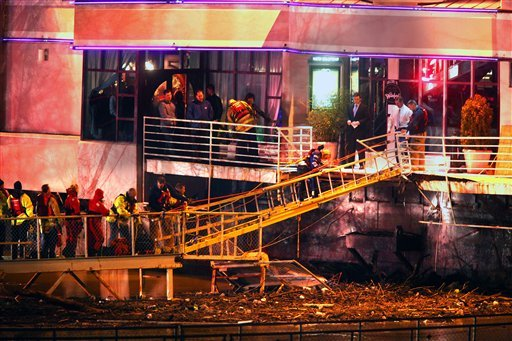 In this Friday, March 11, 2011 photo, a woman walks down a fire ladder, used as an improvised ramp, during a rescue operation in which customers were off-loaded from Jeff Ruby's Waterfront in Covington, Ky. (AP Photo/The Cincinnati Enquirer)