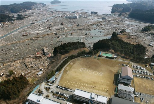 An SOS sign is written on the ground of Shizugawa High School in Minamisanrikucho in Miyagi Prefecture (state), northern Japan, Sunday, March 13, 2011, two days after the powerful earthquake and tsunami hit the area. (AP Photo/Kyodo News).