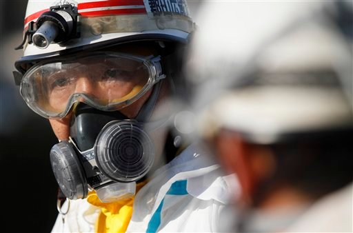 An official wears protective clothing while waiting to scan people for radiation an emergency center on Sunday, March 13, 2011. (AP)
