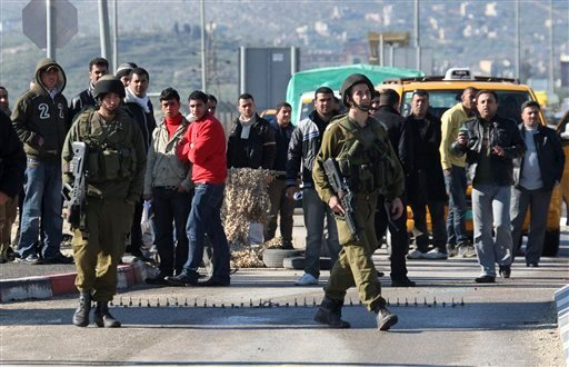 Israeli soldiers man Hawara checkpoint as Palestinians wait to cross, near the West Bank town of Nablus, after five people were killed. (AP Photo/Nasser Ishtayeh)