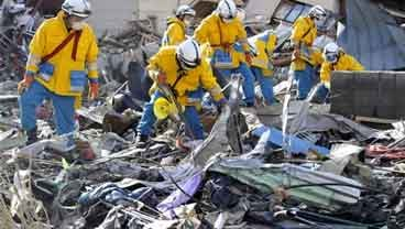 Police officers from Hyogo Prefecture search missing persons in the rubble in Kamaishi, Iwate Prefecture, northern Japan March 14, 2011 following Friday's massive earthquake and the ensuing tsunami. (AP Photo/Kyodo News)