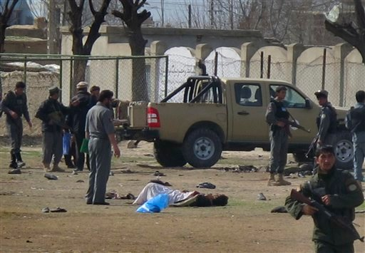 An Afghan victim of a suicide attack, which occurred on Afghan army recruitment center is seen on the ground at the scene of suicide attack in Kunduz, north of Kabul, Afghanistan March 14, 2011. (AP Photo/Fulad Hamdard)