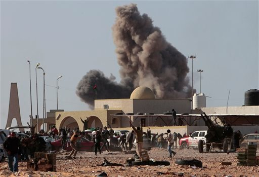 Anti-Gadhafi rebels run away as smoke rises following an air strike by Libyan warplanes near a checkpoint of the anti-Libyan Leader Moammar Gadhafi rebels, in the oil town of Ras Lanouf, eastern Libya, Monday, March 7, 2011.