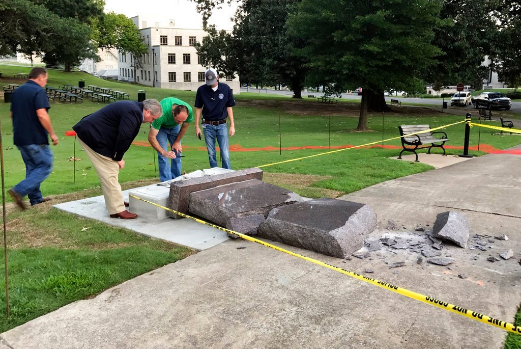 Personnel from the Secretary of State's office inspect the damage to the new Ten Commandments monument outside the state Capitol in Little Rock, Ark.