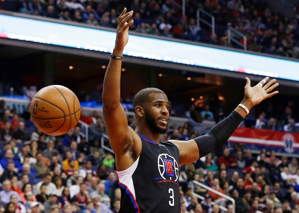 Former Los Angeles Clippers guard Chris Paul reacts after dunking the ball during the first half of an NBA basketball game against the Washington Wizards.