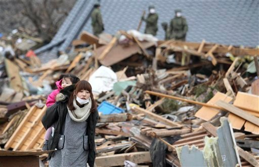 A woman carrying a girl on her back walks in a devastated area during a search operation in Ofunato, Iwate Prefecture, northern Japan, March 15, 2011. (AP Photo/The Yomiuri Shimbun, Masamichi Genko)