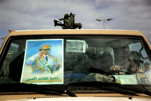A poster of Libyan leader Muammar Qaddafi is displayed on the windshield of a military truck in Tripoli Libya, Tuesday March 8, 2011. (AP Photo/Jerome Delay)