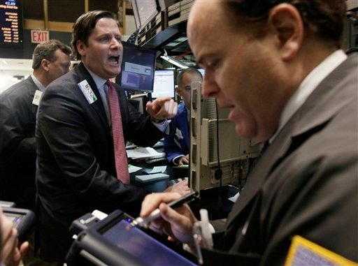 Specialist Gregg Maloney, center, gives prices as he works at his post on the floor of the New York Stock Exchange Tuesday, March 15, 2011. (AP Photo)