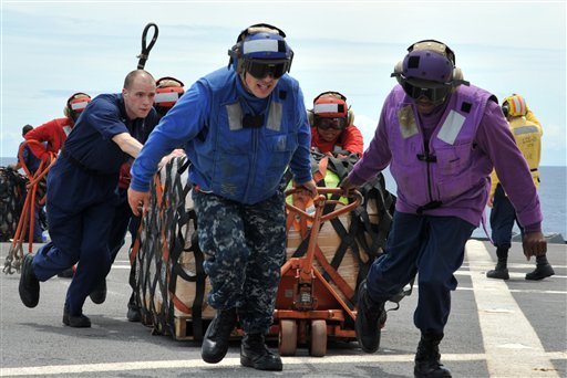 In this Saturday, March 12, 2011 photo released by the U.S. Navy, sailors aboard the U.S. 7th Fleet command ship USS Blue Ridge (LCC 19) in the South China Sea move pallets of humanitarian relief supplies across the ship's flight deck.